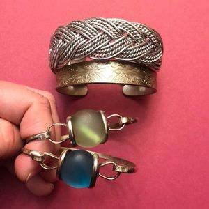 Bundle of silver color bracelets.